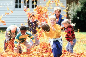 Little kids playing in a pile of leaves